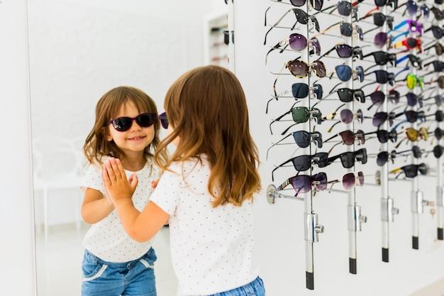 Kind dat zonnebril draagt en in spiegel kijkt