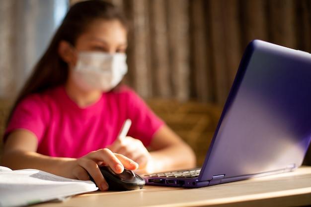 Kind die gezichts medisch masker dragen die thuis bestuderen tijdens coronavirusuitbraak. het jonge schoolmeisje dat afstandsonderwijs heeft werkt bij de computer