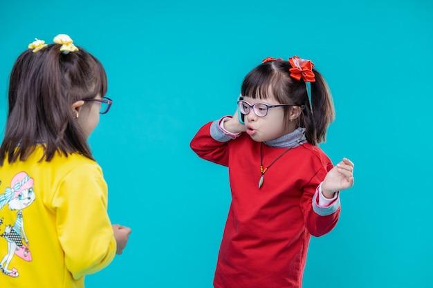 Kind doet alsof praten. twee meisjes met het syndroom van down, kleurrijke outfits dragen en een gesprek voeren op de smartphone