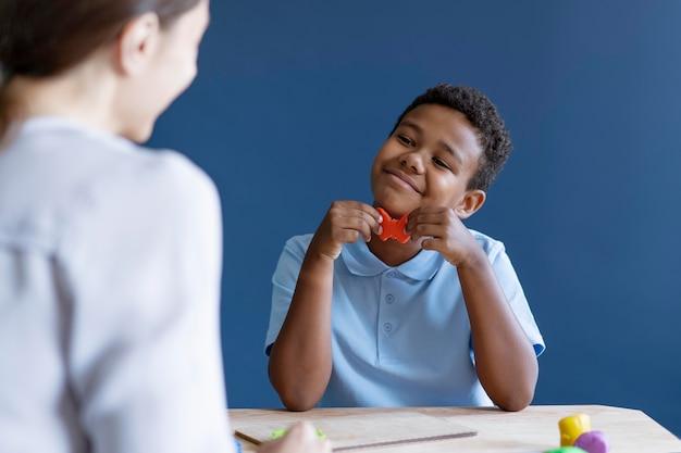 Kind doet een ergotherapiesessie met een psycholoog