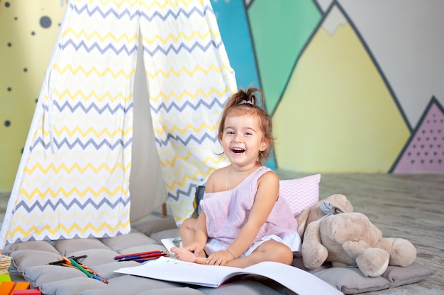 Kind doet huiswerk kind trekt in de kleuterklas. een kleuter leert schrijven en lezen. creatief kind. weinig glimlachend meisje trekt thuis met potloden. concept kinderjaren en kindontwikkeling