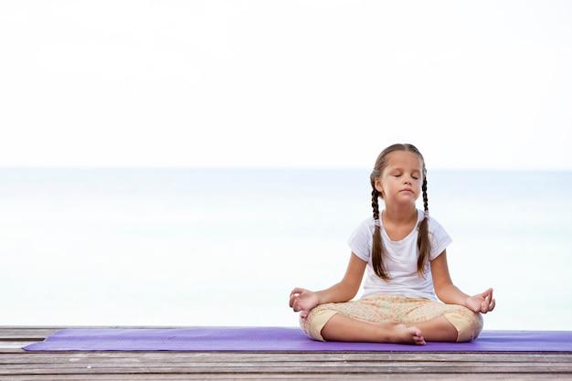 Kind doet oefening op platform buitenshuis. gezonde oceaanlevensstijl. yoga meisje