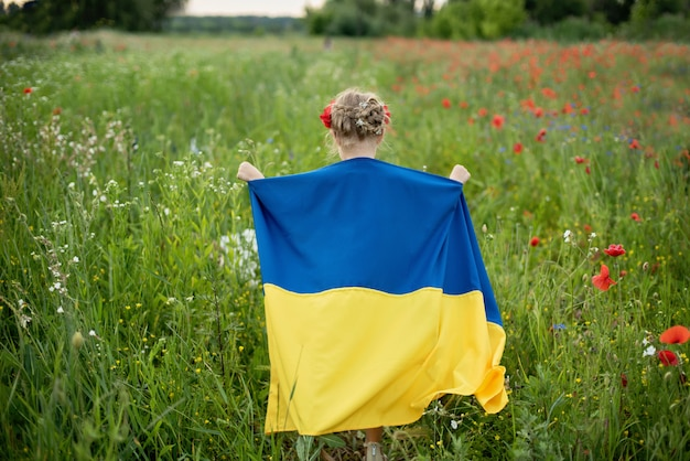 Kind draagt fladderende blauwe en gele vlag van oekraïne in veld. onafhankelijkheidsdag oekraïne. vlaggendag. dag van de grondwet. meisje in traditioneel borduurwerk met vlag van oekraïne.