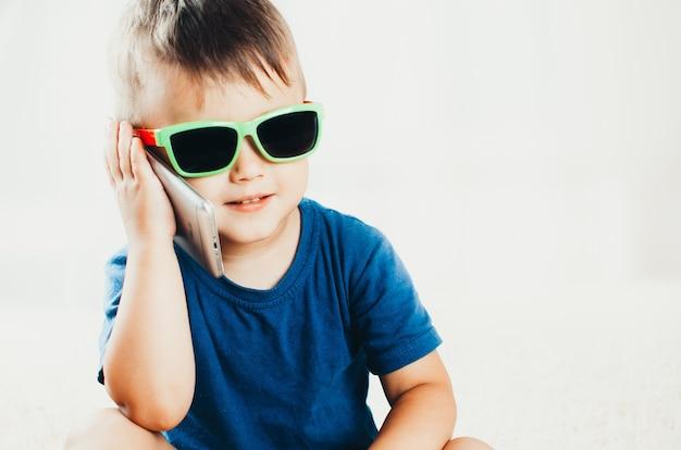 Kind dragen van een zonnebril met smartphone, bedrijfsconcept