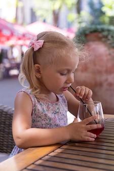 Kind drinkt een drankje op het zomerterras onder natuurlijk licht. echte mensen.