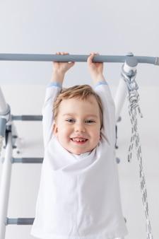 Kind een jongen klimt op de zweedse muur van het huis