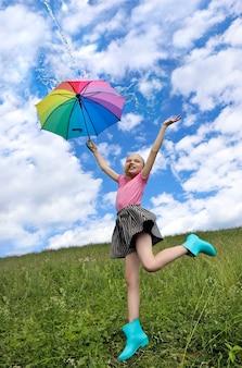 Kind een meisje met een goed humeur springt in de zomer in een veld met een regenboogparaplu waarop water uit de lucht stroomt.