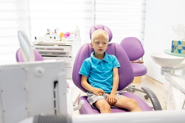 Kind een vijfjarige jongen in een blauw t-shirt zit in een lila stoel in een tandartspraktijk