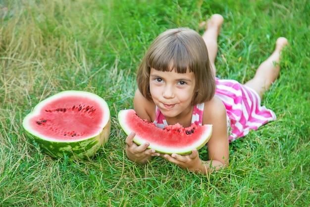 Kind eet een watermeloen in de tuin
