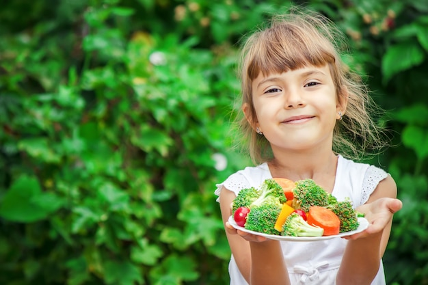 Kind eet groenten. zomerfoto. selectieve aandacht.
