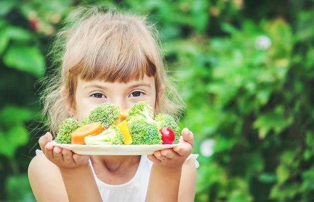 Kind eet groenten. zomerfoto. selectieve aandacht