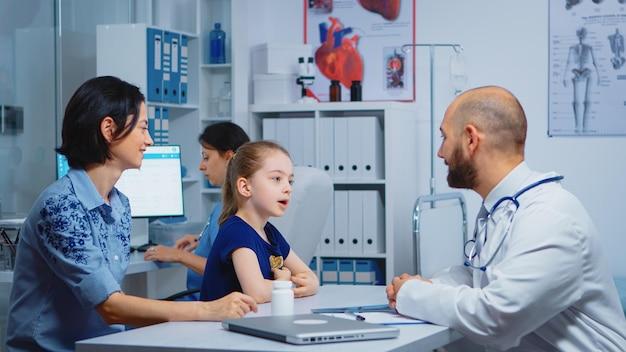Kind en arts praten in de kliniek terwijl verpleegster pillen controleert. kinderarts specialist in geneeskunde verstrekken van gezondheidszorg consultatie diagnostisch onderzoek behandeling in ziekenhuis kabinet