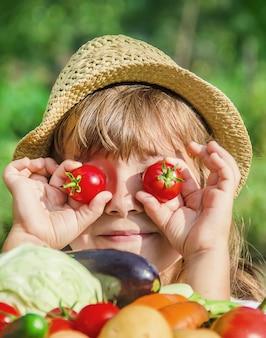 Kind en groenten op de boerderij. selectieve aandacht. nmature.
