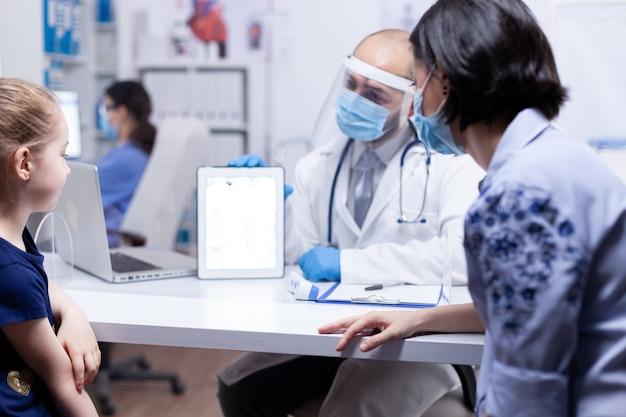 Kind en moeder op doktersafspraak tijdens wereldwijde pandemie met coronavirus