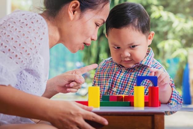 Kind en moeder spelen met houten kleurrijke blokken kleine jongen is van plan toren te bouwen door houten kleurrijke blok educatief speelgoed en thuis leren kinderen concept