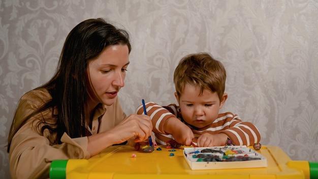 Kind en moeder spelen samen met plasticine