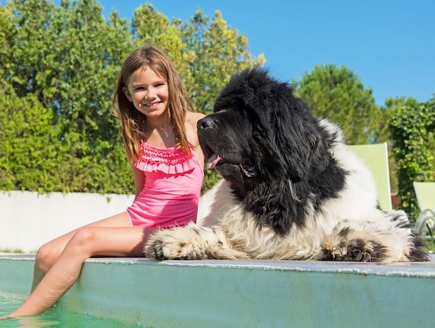 Kind en newfoundland hond in zwembad