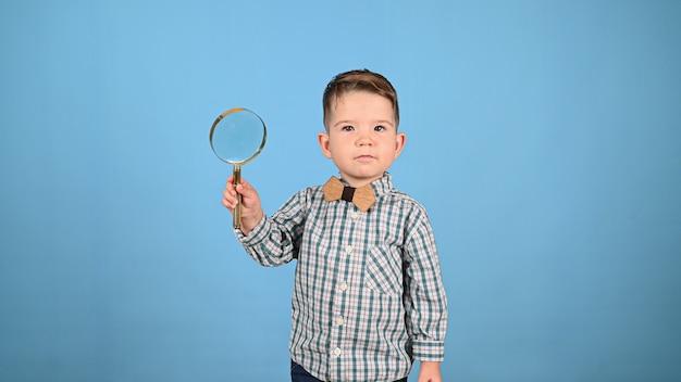 Kind en vergrootglas, op een blauwe achtergrond. hoge kwaliteit foto