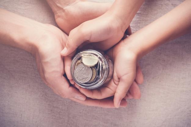 Kind en volwassen bedrijf geld pot, donatie, concept opslaan