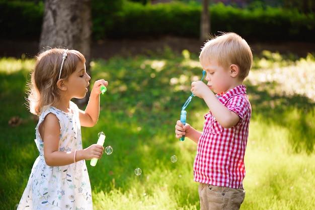 Kind en vrienden spelen een bubbel in de speeltuin met zonsondergang