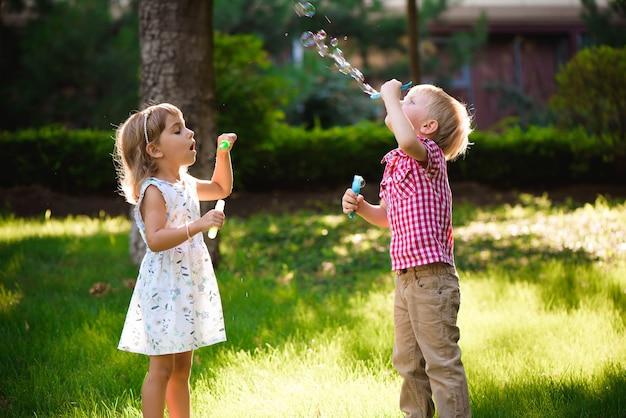 Kind en vrienden spelen een zeepbel in de speeltuin met zonsondergangachtergrond, kind, kind, school, spel en zomerachtergrond