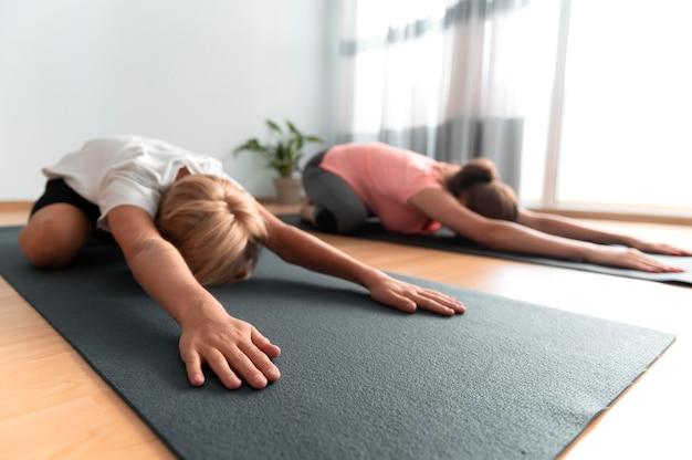 Kind en vrouw met yogamatten full shot