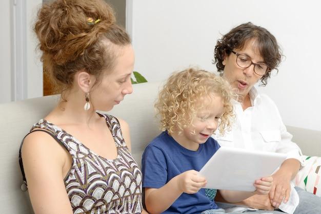 Kind en zijn moeder met grootmoeder spelen met tablet