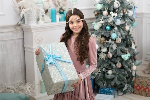 Kind enthousiast over haar geschenk. kid klein meisje in elegante jurk en geschenkdoos kerstboom achtergrond. kerstcadeau. klein meisje ontving vakantiegift. beste kerstcadeaus. winterse verrassing.