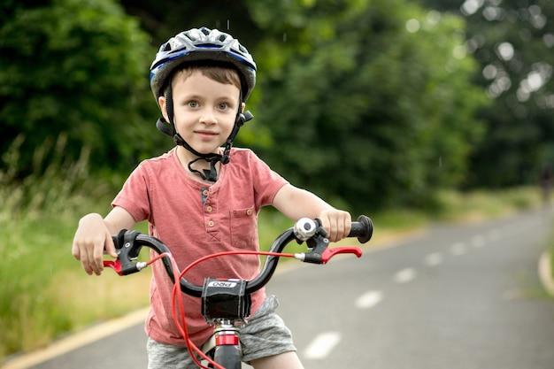 Kind fietsten op het fietspad bij regen. kid in helm leren rijden in de zomer. gelukkige jongen fietsten, plezier buitenshuis op de natuur. actieve sport familie vrije tijd