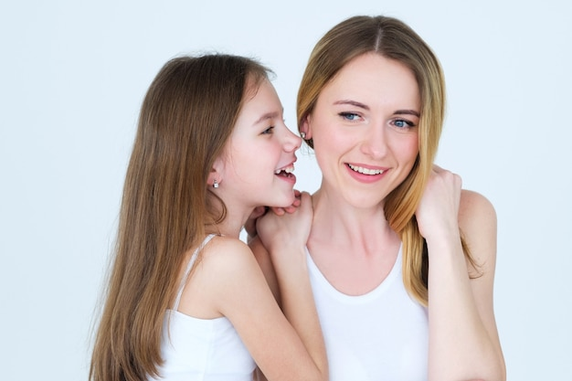 Kind fluisterde iets in het oor van haar moeder.