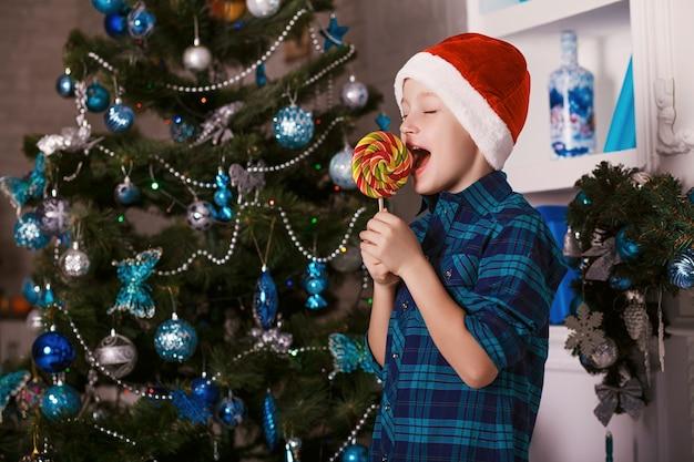 Kind gelukkig eten snoep in de buurt van de kerstboom