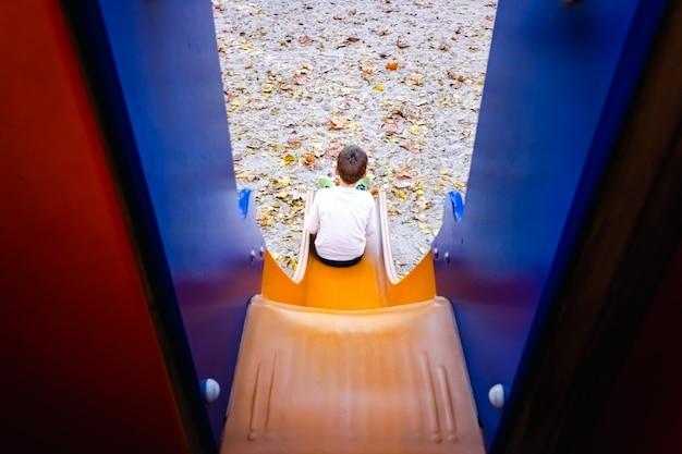 Kind glijdt van een glijbaan, van achteren gezien van bovenaf.