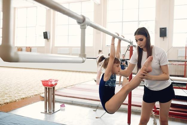 Kind gymnastiek evenwichtsbalk. meisje gymnast atleet tijdens een oefening horizontale balk in gymnastiek wedstrijden. coach met kind.
