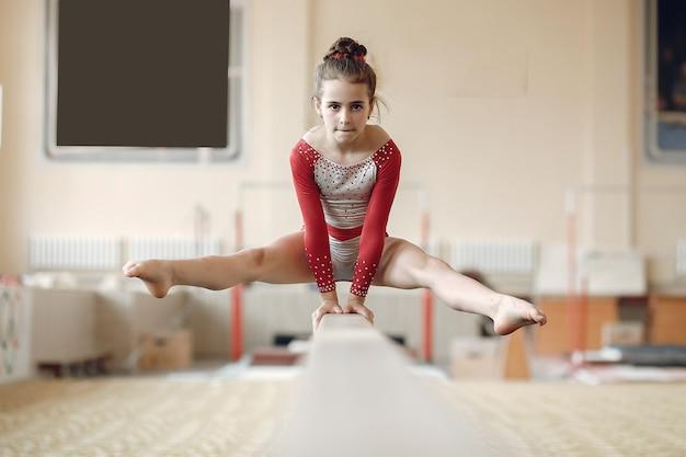 Kind gymnastiek evenwichtsbalk. meisje gymnast atleet tijdens een oefening horizontale balk in gymnastiek wedstrijden.