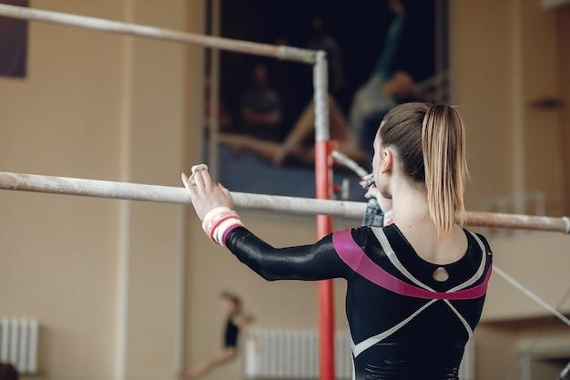 Kind gymnastiek evenwichtsbalk. vrouw gymnast atleet tijdens een oefening horizontale balk in gymnastiek wedstrijden.