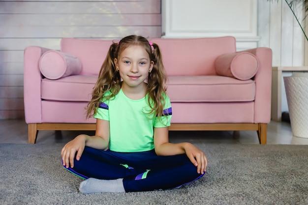 Kind gymnastische yoga-oefeningen doen en glimlachen