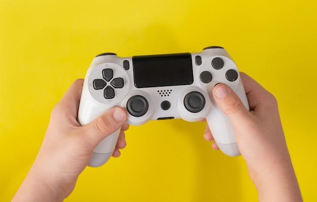 Kind hand met witte spelbesturing op geel oppervlak