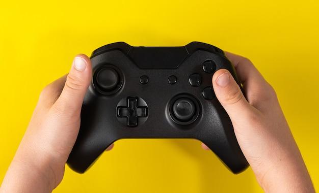 Kind hand met zwarte spelbesturing op geel oppervlak