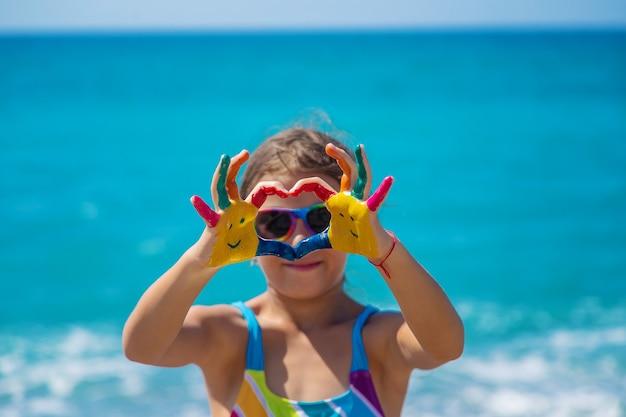 Kind handen beschilderd met verf op de zee. selectieve aandacht. kind.