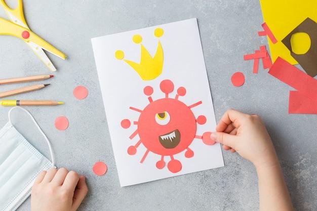 Kind handen maken kaartcollage met corona virus covid-19