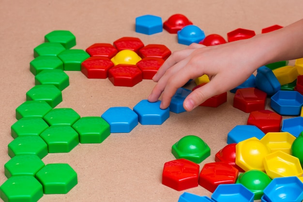 Kind handen spelen met gekleurde mozaïek puzzel