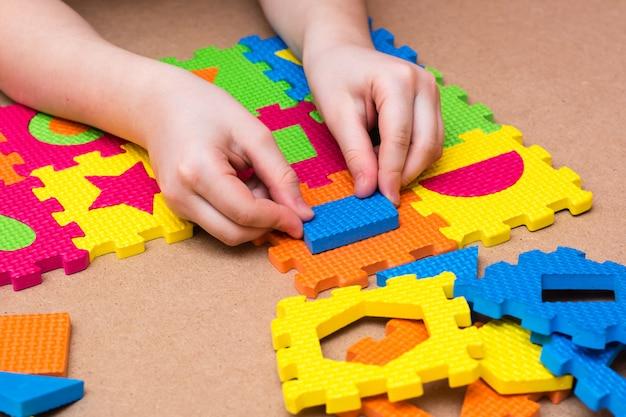 Kind handen spelen met gekleurde puzzel