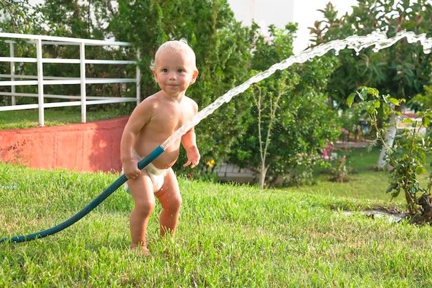 Kind het gras in de tuin water geven