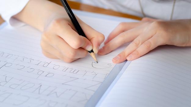 Kind het schrijven alfabet in notitieboekje tijdens corona-virusslot neer. thuisonderwijs en kinderen in quarantaine.