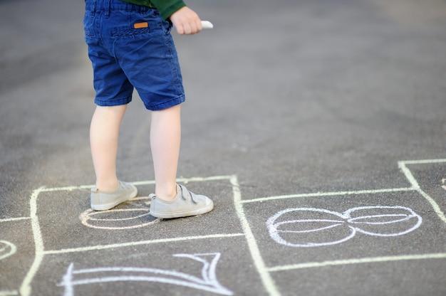 Kind het spelen hinkelspelspel op speelplaats in openlucht op een zonnige dag