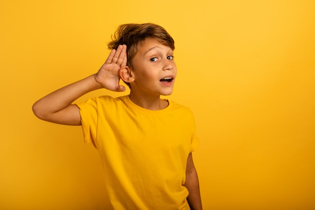 Kind hoort een geheime mededeling. concept van nieuwsgierigheid en roddel. verbaasde uitdrukking