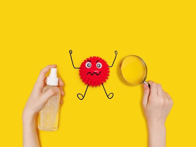 Kind houdt antiseptische spray vast en ziet cartoon covid-19-bacteriën op tafel door een vergrootglas.