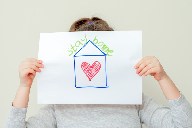 Kind houdt foto van huis vast.