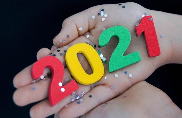 Kind houdt in zijn hand veelkleurige nummers 2021 op een zwarte achtergrond