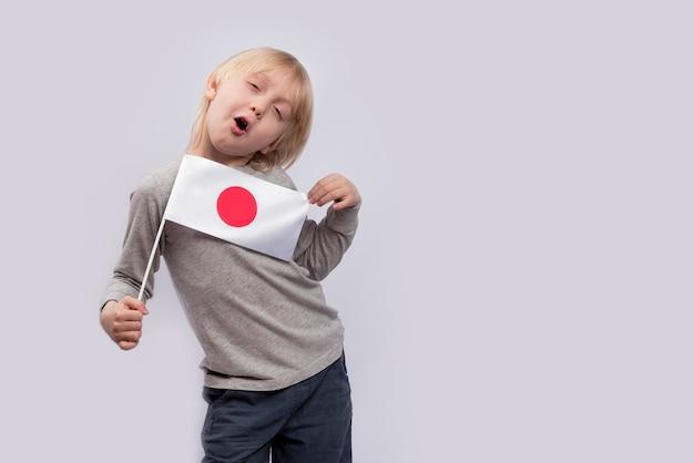 Kind houdt vlag van japan vast en maakt gezichten. vrolijke jongen met japanse vlag.